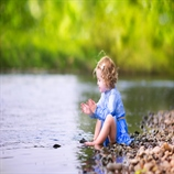 Adorable curly toddler girl wearing a blue dress playing at a river shore throwing stones into the water on a hot sunny summer day